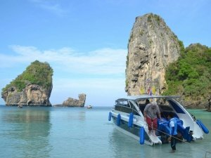 customer is helped from private boat at island in phang nga bay
