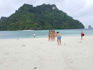 ladies in bikinis pose for a photo at tub island with chicken island in the background